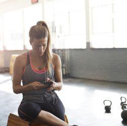Femme sur son téléphone dans une salle de sport