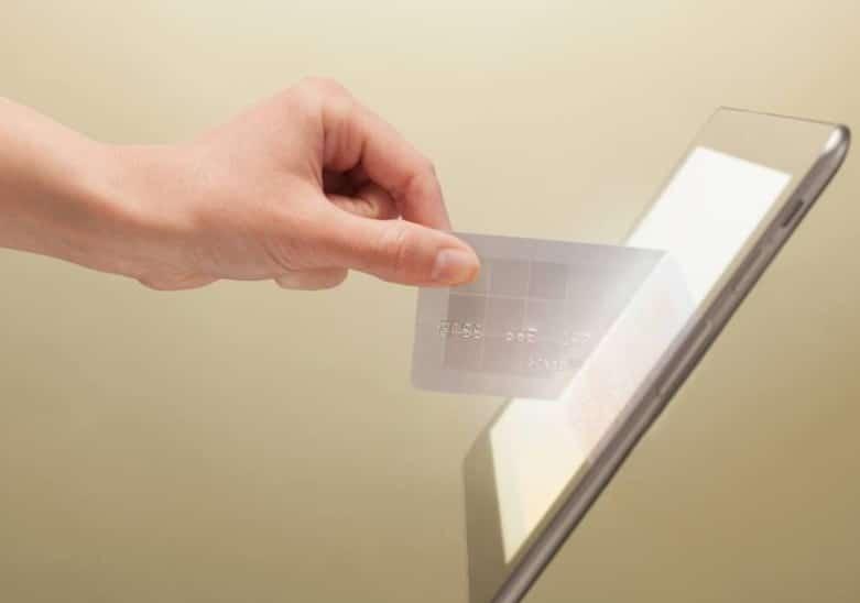 Main qui passe une carte bancaire à travers un écran de tablette