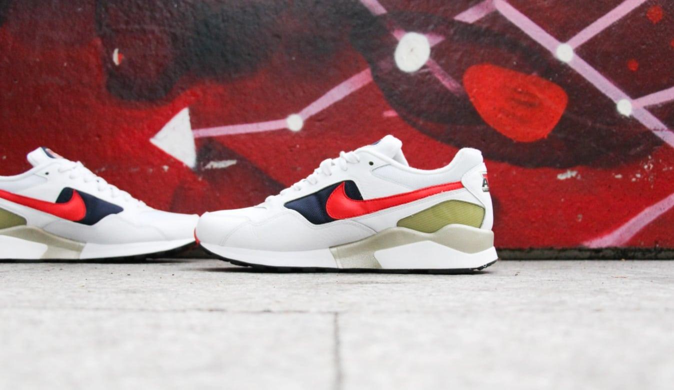 Paire de chaussures nike devant un mur rouge